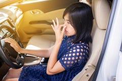 De vrouwenhand drukt haar neus met van stank in een auto stock fotografie