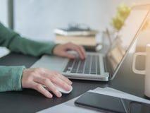 De vrouwenhand gebruikt laptop thuis met draadloze muis op bureau stock foto