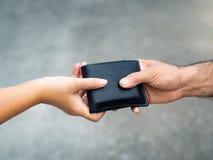 De vrouwenhand geeft de portefeuille aan de man Geld & Financiële mede royalty-vrije stock foto's