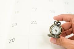 De vrouwenhand houdt een klassiek uitstekend halsbandhorloge op kalender dat Stock Foto's