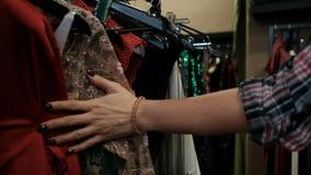 De vrouwenhand houdt op kleren met armband, zwarte manicure in geruit stock video