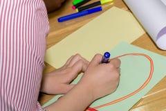 De vrouwenhand met rood voelde het hart van de pentekening op groot Witboek met stickman op bureau in klaslokaal stock fotografie