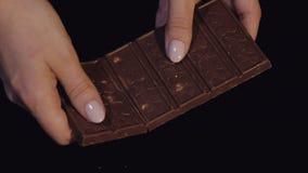 De vrouwenhand neemt één stuk van chocoladereep van een bos van chocoladestukken Langzame Motie stock videobeelden