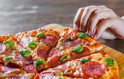 De vrouwenhand neemt een plak van Pepperonispizza met Mozarellakaas, salami, Tomaten, peper, Kruiden en Vers Basilicum Italiaanse stock foto's