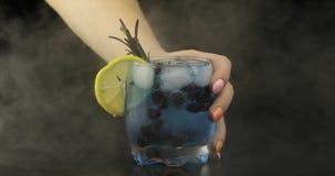 De vrouwenhand neemt de verfrissende blauwe cocktail van de sodalimonade royalty-vrije stock afbeelding
