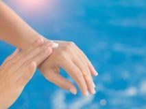 De vrouwenhand past zonnescherm/sunblock door het zwembad toe royalty-vrije stock foto's