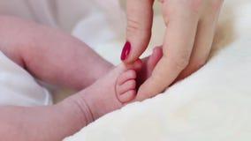 De vrouwenhand raakt grappige kleine voeten van baby op bed in ruimte stock videobeelden