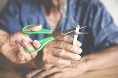 De vrouwenhand sneed sigaret van haar vader door schaar, ophoudt rokend concept royalty-vrije stock foto's