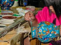 De vrouwenhand verfraaide een porseleinvaas met een druppelbuisje Stock Fotografie