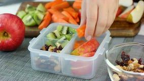 De vrouwenhand zette gezonde fruit en nootsnacks in de lunchdoos