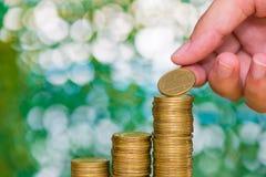 De vrouwenhand zette muntstuk op stap van muntstukkenstapels en gouden muntstukgeld Stock Afbeelding