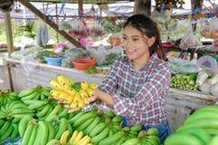 De vrouwenhandelaar verkoopt groenten, vruchten en bananen die rijpe geel in een landelijke kant van de wegwinkel Thailand zijn stock afbeelding