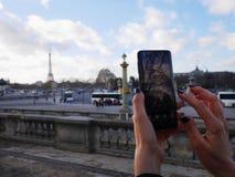 De vrouwenhanden die de telefoon houden en nemen een beeld van de toren van Eiffel in stedelijke ruimte royalty-vrije stock fotografie