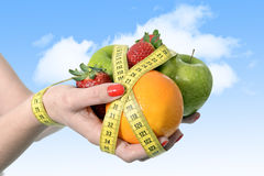 De vrouwenhanden met mengeling van fruit plakken pols met maatregelenband wordt in het op dieet zijn verpakt die Stock Foto