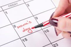 De vrouwenhanden met rood vonden de pen de dag van woordenmamma's in kalender schrijft stock foto's