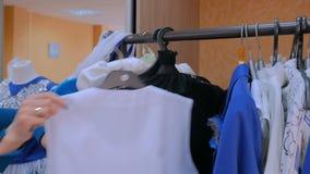 De vrouwenhanden regelt hanger met kleren stock footage