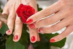 De vrouwenhanden wat betreft rood namen toe Stock Foto