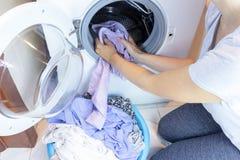 De vrouwenhuisvrouw trekt de wasserij uit of laadt een wasmachine royalty-vrije stock afbeelding