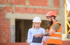 De de vrouweningenieur en bouwer delen bouwwerf mee Communicatie van het bouwteam concept Verband tussen stock afbeeldingen