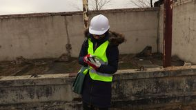 De vrouweninspecteur neemt beelden op smartphone bij bouw van een gebouw stock footage