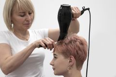 De vrouwenkapper maakt kapsel in een schoonheidssalon stock foto