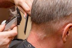 De vrouwenkapper snijdt man haar met elektrische clipper snoeischaar stock foto's