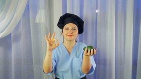 De vrouwenkok in schort glimlacht, houdt avocado in haar hand en toont o.k. met haar hand stock videobeelden