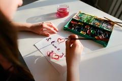 De vrouwenkunstenaar in cursief schrijft cursieve inschrijving op document s Royalty-vrije Stock Foto