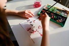De vrouwenkunstenaar in cursief schrijft cursieve inschrijving op document s Stock Afbeeldingen