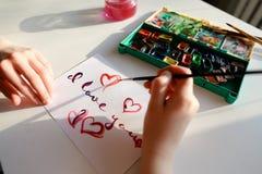 De vrouwenkunstenaar in cursief schrijft cursieve inschrijving op document s Stock Foto