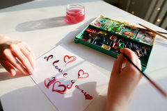 De vrouwenkunstenaar in cursief schrijft cursieve inschrijving op document s Stock Afbeelding