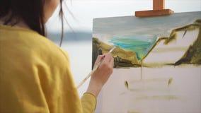 De vrouwenkunstenaar schildert een olieverfschilderij op canvas, dat zich op een schildersezel bevindt stock videobeelden