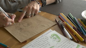 De vrouwenkunstenaar trekt illustraties voor een boek van kinderen met potloden stock footage