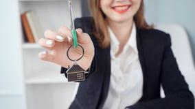 De vrouwenmakelaar in onroerend goed geeft de sleutels aan een flat aan cliënten stock videobeelden