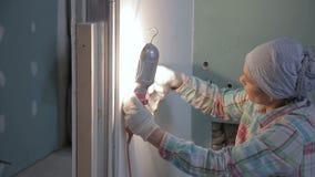 De vrouwenmeester maakt de muur van ruimte vóór reparatie schoon stock videobeelden