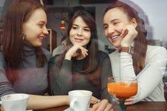 De vrouwenmeisjes in een koffie hebben een pret die en hun dranken babbelt drinkt Mening van achter glas stock fotografie
