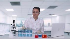 De vrouwenmicrobioloog analyseert de vloeistof in een de gedragingen van de reageerbuisa vrouwelijk wetenschapper medisch onderzo stock video