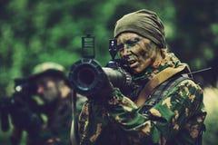 De vrouwenmilitair met een granaatlanceerinrichting in van hem dient bos in stock foto