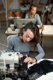 De vrouwennaaisters werken aan naaimachines royalty-vrije stock afbeelding