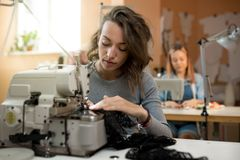 De vrouwennaaisters werken in de workshop aan naaimachines royalty-vrije stock afbeeldingen