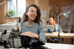 De vrouwennaaisters werken in de workshop aan naaimachines stock foto