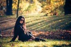 De vrouwenontspanning van de schoonheid op het groene gras Stock Afbeeldingen