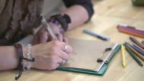 De vrouwenontwerper denkt over lay-out van kaarten met een groet op lijst met veel kleurpotloden stock video
