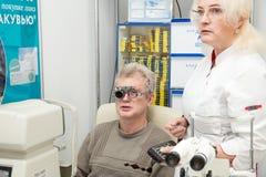 De vrouwenoptometrist controleert visie van een man Stock Foto