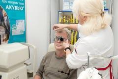 De vrouwenoptometrist controleert visie van een man Stock Foto's