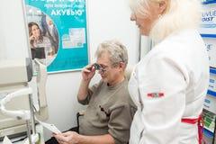 De vrouwenoptometrist controleert visie van een rijpe man Stock Afbeeldingen