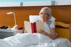 De vrouwenpatiënt leest een boek, terwijl het liggen in het het ziekenhuisbed Royalty-vrije Stock Afbeeldingen