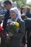 De vrouwenportret van de oorlogsveteraan Zij houdt bloemen en glimlacht Stock Fotografie