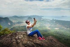 De vrouwenreis zit op een klip op een rijke bosberg Tab Kak Hang Nak Hill-Aardsleep selfie Stock Fotografie