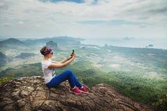 De vrouwenreis zit op een klip op een rijke bosberg Tab Kak Hang Nak Hill-Aardsleep selfie Royalty-vrije Stock Afbeeldingen
